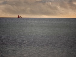 Galway hooker boat in the ocean with traditional red color sail, Atlantic ocean, Cloudy sky. Water surface.