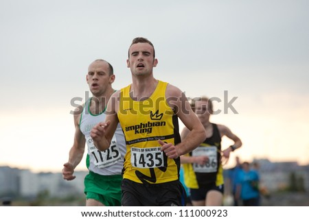 GALWAY, IRELAND - AUGUST 11: Peadar  Harvey and other athletes compete during annual Corrib Oil Streets of Galway 8K road race, on August 11, 2012 in Galway, Ireland. - stock photo