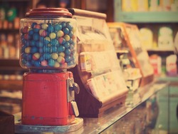 gamble eggs in vintage gumball machine on glass counter at grocery store, vintage filter effect
