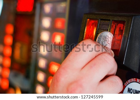 Gambler inserts dollar into slot machine