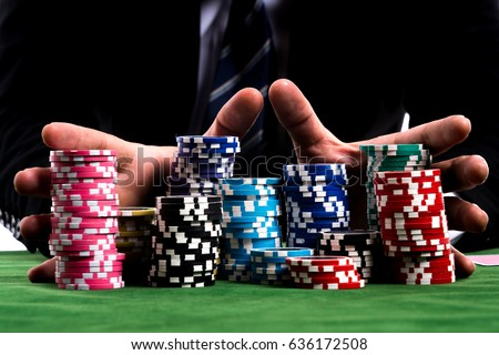 Gambler man hands pushing large stack of colored poker chips across gaming table for betting