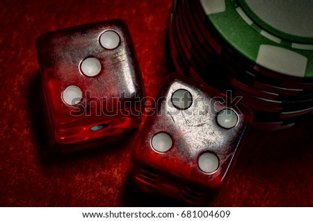 Gambling and betting addiction concept with a grunge closeup image of dice  and casino chips on a red felt with scratches on each die and dirt on the chips
