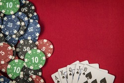 Gambling chips and card for poker on red felt background