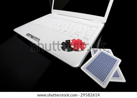 Gambling chips and cards on white laptop computer.