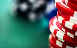 Gambling chips stacks on green felt table copy space