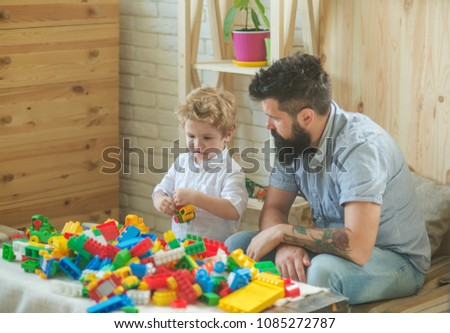 Game, childhood, father teaches the boy to play with cars and plastic blocks. Build a house, rest with children. Childhood and development. Beautiful cozy house and a happy family #1085272787