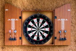 Game Dart board on wooden background