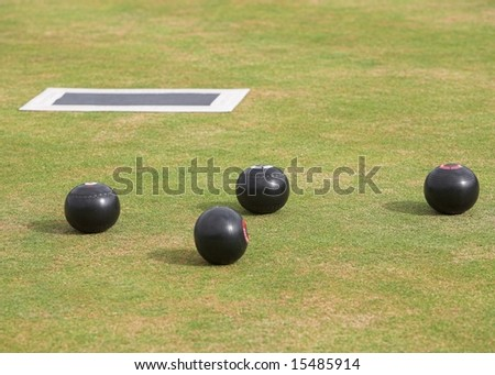 Game of lawn bowls with bowling woods and mat. - stock photo