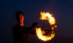 Game of light and dark. Fire spinner at night. Happy male spinner spin burning poi. Fire performance. Poi spinning and flow art. Evening party. Outdoor festival. Celebrating holidays.