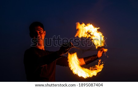 Game of light and dark. Fire spinner at night. Happy male spinner spin burning poi. Fire performance. Poi spinning and flow art. Evening party. Outdoor festival. Celebrating holidays. Photo stock ©