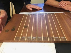 Game of shove ha'penny showing board, coins and action. Board game, family game, pub game, shove halfpenny Shuffleboard tabletop slype groat, slide-thrift