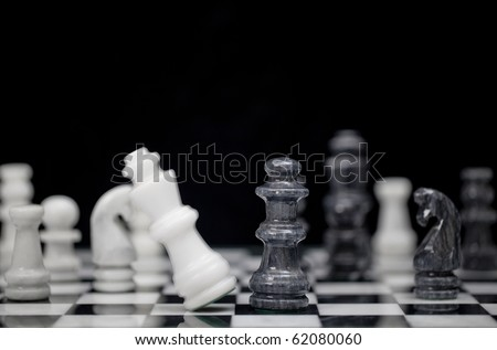 Game Over - the king on a chess board falling having just been taken by the opposing queen