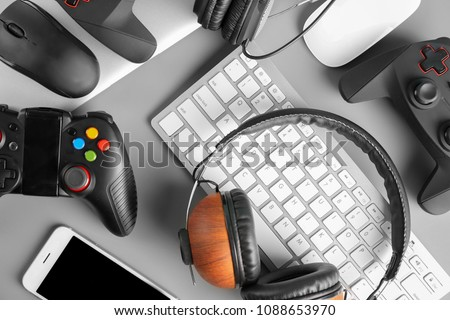 Gamepads, mice, headphones and keyboard on table #1088653970