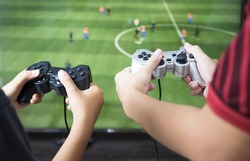 Gamer hand playing video game  at home.Boy friends group enjoy and relax with football game online on TV.Stay at home concept.