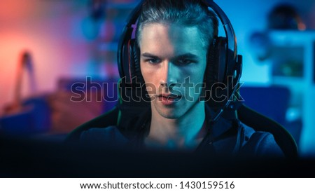 Gamer in Headset with a Mic Playing Online Video Game on His Personal Computer. He is Focused on Monitor. Room and Personal Computer have Colorful Neon Led Lights. Cozy Evening at Home. #1430159516