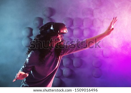 gamer in virtual reality, girl plays a game or explores the environment in a simulation. young woman in VR helmet touches something. Modern technologies, concept