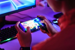 Gamer playing online game on smart phone in dark room. e-Sport Games compilation and Internet Championship.