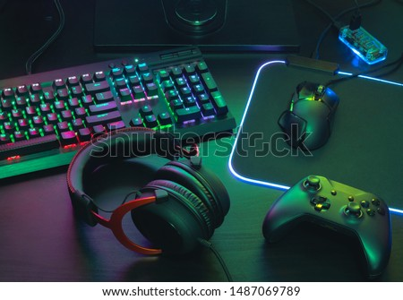 Photo of  gamer work space concept, top view a gaming gear, mouse, keyboard, joystick, headset, mobile joystick, in ear headphone and mouse pad with rgb color on black table background.