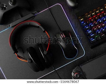 gamer workspace concept, top view a gaming gear, mouse, keyboard, joystick, headset, mobile joystick and mouse pad on black table background with RGB color. #1164678067