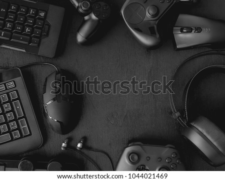 gamer workspace concept, top view a gaming gear, mouse, keyboard, joystick, headset on black table background with copy space. #1044021469