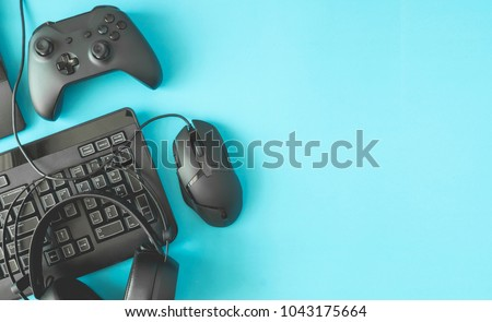 gamer workspace concept, top view a gaming gear, mouse, keyboard, joystick, headset on blue table background with copyspace.