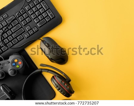 gamer workspace concept, top view a gaming gear, mouse, keyboard, joystick, headset, on yellow table background with copy space #772735207