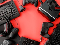 gamer workspace concept, top view a gaming gear, mouse, keyboard, joystick, headset, VR Headset on red table background with copy space