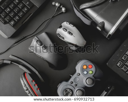 gamer workspace concept, top view a gaming gear, mouse, keyboard, joystick, headset, webcam, VR Headset on black table background. #690932713