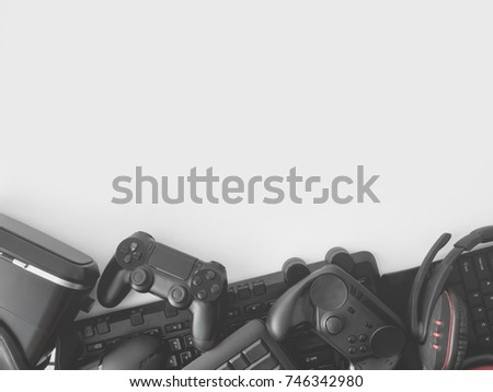 gamer workspace concept, top view a gaming gear, mouse, keyboard, joystick, headset, webcam, VR Headset on black table background.