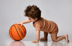 Games for children. Playful curly baby boy dressed in a brown bodysuit with interest plays a basketball on a gray background. Concept of new for children. Place for text.