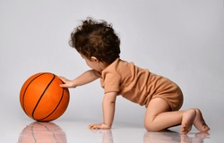 Games for children. Playful curly kid in a brown bodysuit plays basketball with interest on a gray background. The concept of new to children. Place for text.