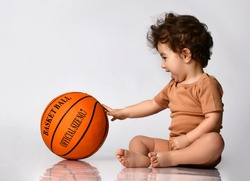 Games for children. Playful curly little boy dressed in a bodysuit sitting barefoot and playing a new basketball on a gray background. Place for text. Concept of active childhood.