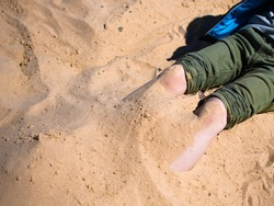 games on the beach. a little boy's feet are buried in the sand. summertime