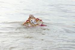Ganesha idol in water with use of selective focus on a particular part of the idol with rest of the idol, the water and background blurred.