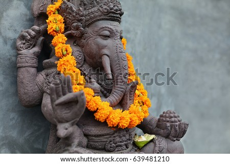 Ganesha with balinese Barong masks sitting on front of temple. Decorated for religious festival by orange flowers necklace and ceremonial offering. Travel background, Bali island art and culture. #639481210