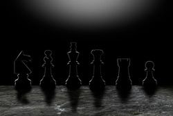 Gang of outlined chess pieces on black background