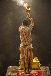 Ganga aarti performed in the evening by an unidentified priest at the Dashashwamedh Ghat. Ganga Aarti is performed at the three holy cities of Haridwar, Rishikesh, and Varanasi, India.