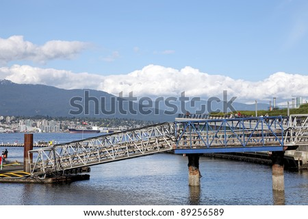 Gangplank from quay to landing stage of seaplanes on a gulf, city and mountain tops background. Vancouver, Canada.