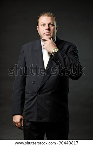 Gangster mafia man in suit with tie looking tough isolated on dark background