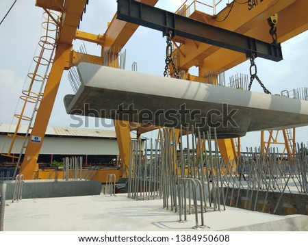 Gantry crane is lifting the precast concrete of pier cap for one of elevated structure project in Malaysia. #1384950608