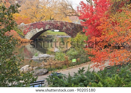 Gapstow Bridge on the Central Park Pond covered in red ivy and surrounded by beautiful fall foliage in New york City