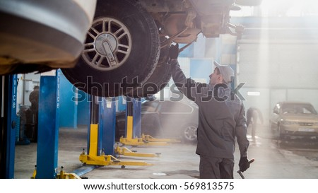 Garage automobile service - a mechanic checks the transmission Foto stock ©