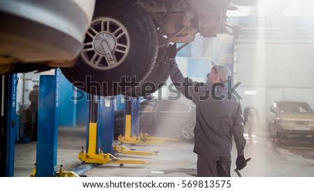 Garage automobile service - a mechanic checks the transmission Foto stock ©