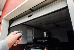 Garage door PVC. Hand use remote controller for closing and opening garage door.