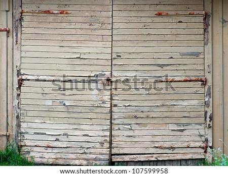 Garage door with peeling yellow paint and rusty metal details #107599958