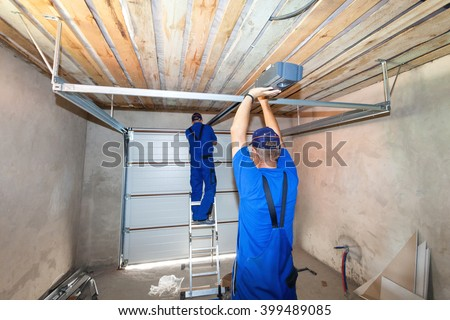 Garage doors installation.Workers installing lifting system