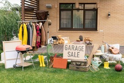 Garage sale in backyard: various toys, household stuff and clothes putting on sale