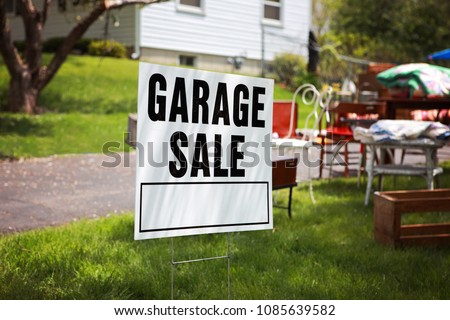 Garage sale sign on the lawn of a suburban home