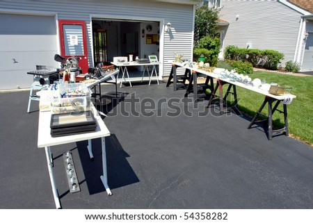Garage sale with junk and odd objects for sale on tables on a suburban house yard driveway