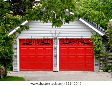 Garage with red doors in green setting